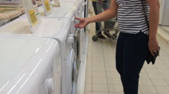 Woman choosing washing machine in white goods store Stock Footage