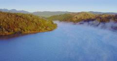Aerial of sunrise on whangamata estuary and hills, Coromandel, New Zealand Stock Footage