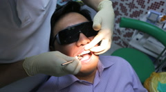 Dentist is healing client teeth with mouth mirror Stock Footage