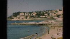1948: Seaside resort sometime in the 1960s with beachgoers and cabanas..PORTUGAL Stock Footage
