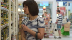 Woman buying can olives in grocery store Stock Footage