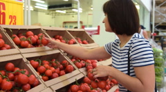Woman buying tomatoes in the grocery Stock Footage