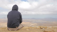 Boy wearing a hooded sweatshirt contemplates the desert Stock Footage