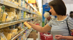 People shopping in dairy section of supermarket Stock Footage