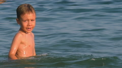 Boy learning to swimming in salt water of the sea Stock Footage