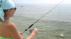 Sea fishing to spinning. Woman with spinning catching fish. Stock Footage