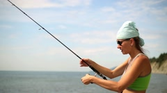 Woman with spinning catching fish. Sea fishing to spinning. Stock Footage