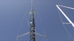 Pan from top of mast of a docked sailboat to anchor on bow as seen looking st Stock Footage