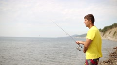 Man with spinning catching fish. Fisherman on the beach. Sea fishing to spinning Arkistovideo