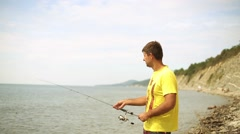 Man throws spinning. Sea fishing to spinning. Fisherman on the beach. Arkistovideo