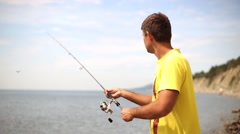 Man with spinning catching fish. Sea fishing to spinning. Fisherman on the beach Arkistovideo