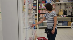Woman looking over fridges in the hypermarket Stock Footage