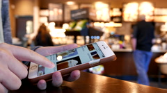 Motion of woman browsing Starbucks drink menu on phone Stock Footage