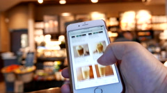 Motion of man browsing Starbucks drink menu on phone Stock Footage