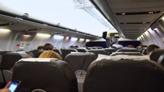 Interior of airplane with passengers on seats waiting to taik off Stock Footage