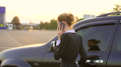 Business woman talking at phone near her crossover car Stock Footage