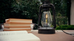 Kerosene lamp and stapka old books on the table in the garden. hand puts the Stock Footage