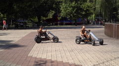 Two boys ride on Kids pedal car. Town Square Stock Footage