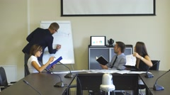 Colleagues discussing graphs in the conference room Stock Footage