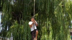 Teenager on the bungee rides. Rope tied to a tree Stock Footage