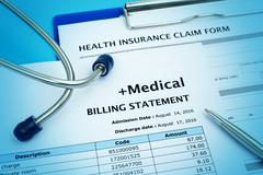 Healthcare cost concept with medical bill and health insurance claim form Stock Photos