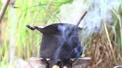 Black old dirty pot with smoke on flame in the northern of Thailand Stock Footage