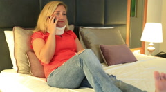 Painful woman with a neck brace talking on the phone Stock Footage