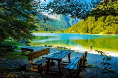 Wooden benches and a table with astonishing view on lake, and tw Stock Photos