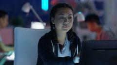 4K Portrait smiling computer game designer working at her desk Stock Footage