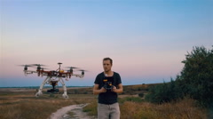 Custom hexacopter flies over a man and flies out of the frame. Slow motion. Stock Footage