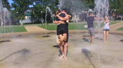 Girls and boys play in the fountain - laughing and kissing Stock Footage