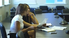 Two businesswomen in discussion of the conditions considering the graphics Stock Footage