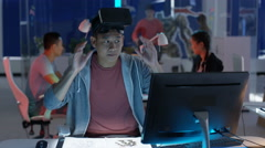 4K Young computer game designer working at his desk & looking into VR viewer. Stock Footage