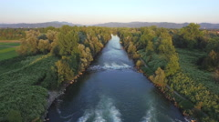 AERIAL: Beautiful wide green river with blooming bushes on rocky riverbank Stock Footage