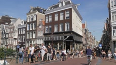 Busy road with tourists in street with old houses,Amsterdam,Netherlands Stock Footage