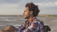 Pensive young afro american man relaxing at the beach  Stock Footage