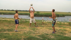 Father and two sons playing with a ball on the lake Stock Footage