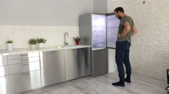 Young man checking new fridge at his new home Stock Footage