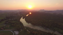 AERIAL: Mystic small town, beautiful river and lush forest at golden sunrise Stock Footage