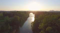 AERIAL: Magical golden sunset over wide fast current river with rocky bottom Stock Footage