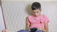 Boy with smartphone and headphones listening to music or playing game at home Stock Footage