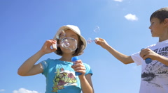 Boy And Girl Blowing Soap Bubbles Outdoors On A Sky Background, Slow Motion Stock Footage