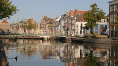 Canal and old houses with cyclists on bridge,Leiden,Netherlands Stock Footage