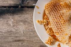 White plate with section of wax honeycomb from beehive on the vintage wooden Stock Photos