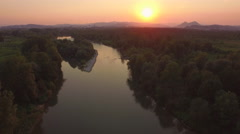 AERIAL: Stunning wide river with small island at magical golden light sunset Stock Footage