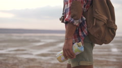 Afro american man traveler with back pack walking at the beach holding map  Stock Footage