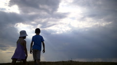 Boy With Girl Walking At Sunset On a Background Of Beautiful Clouds, Sun's Rays Stock Footage
