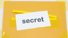 Stop motion hiding the paper with word top secret into yellow zipper Stock Footage