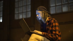 Guy using his laptop at nigth on the street Stock Footage