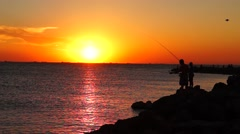 Fisher and gulls on sea at sunset Stock Footage